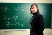 Math teacher against the blackboard — Stock Photo