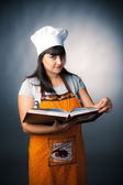 Woman cook holding a recipes book — Stock Photo