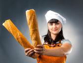 женщина повар холдинг сломанной французский хлеб, фокус на хлеб — Стоковое фото