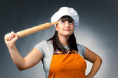 Thoughtful woman cook holding a rolling pin — Stock Photo