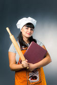 Woman cook with book and rolling pin — Stock Photo