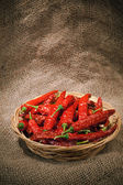 Red chili peppers on the wicker dish — Stock Photo