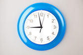 Blue office clock on grey wall — Стоковое фото