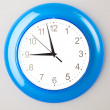 Blue office clock on grey wall — Stock Photo #9475677