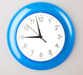 Blue office clock on grey wall — Stok fotoğraf