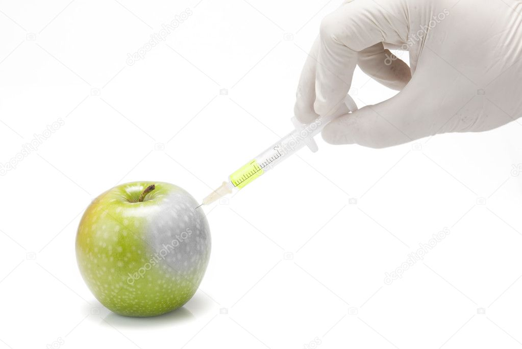 A gloved hand injecting an apple with a syringe on a white background. — Stock Photo #10146190