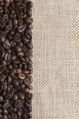 Burlap background with coffee beans. — Stock Photo