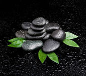 Zen stones and leaves with water drops. leaf and basalt stones. — Stock Photo