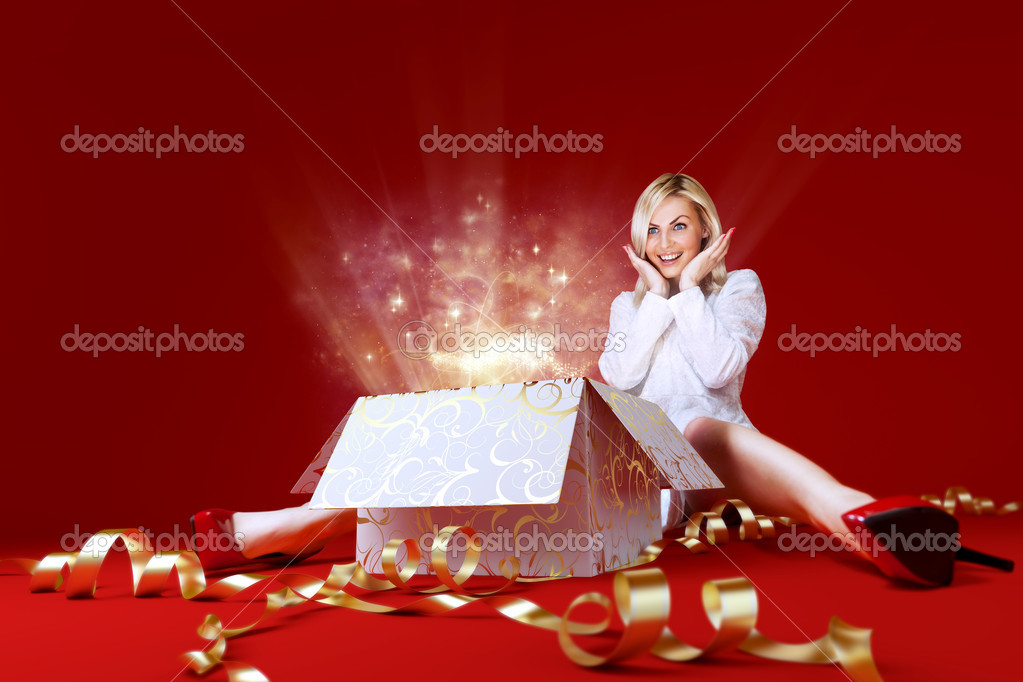 Charming girl in white dress spread shot. Gift box in center. Light beams and stars coming from the box. Red background. Amazing face expression. Sense of holiday.  — Stock Photo #9486626