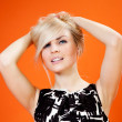 Charming blonde is looking at you! Lady against orange background wearing fashionable b-w dress studio shot — Stock Photo