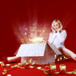 Majestic gift for a pretty blonde! Sense of holiday. Charming girl in white dress spread shot. Gift box in center. Red background. Amazing face expression - Stock Photo