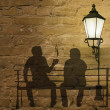 Two silhouettes on a bench — Stock Photo