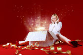 Majestic gift for a pretty blonde! Sense of holiday. Charming girl in white dress spread shot. Gift box in center. Red background. Amazing face expression — Стоковое фото