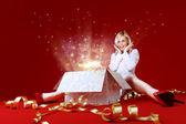 Majestätiska present till en söt blondin! känslan av semester. charmig flicka i vit klänning spread skott. presentförpackning i centrum. röd bakgrund. fantastiska ansikte uttryck — Stockfoto
