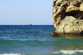 Sailboat and rock on coast — Stock Photo