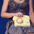 Girl with yellow telephone set on blue background — Stock Photo