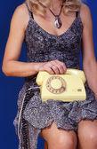 Chica con teléfono amarillo sobre fondo azul — Foto de Stock