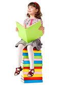 Niña sentada sobre una pila de libros — Foto de Stock