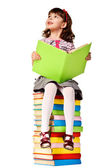 Little girl sitting on stack of books. — Stock Photo