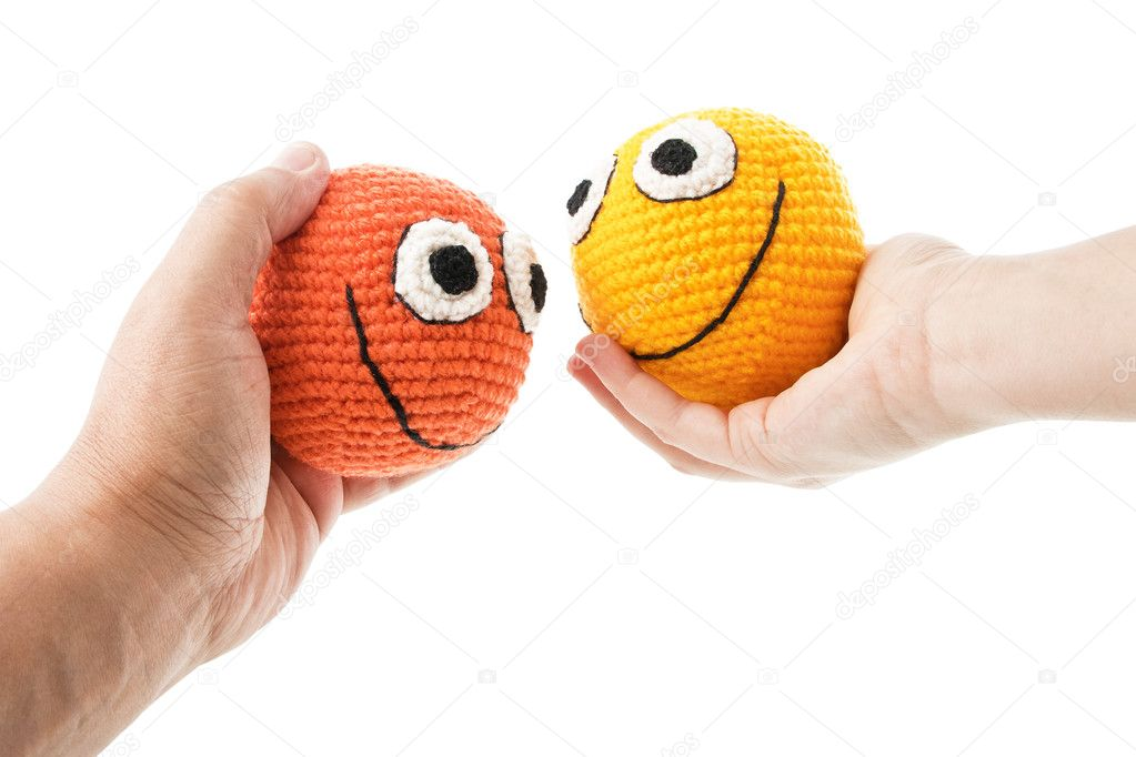 Two crochet smileys in woman and man hands looking to each other. Isolated on white background. — Stock Photo #10045866