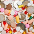 Lot of pills with coins among them — Stock Photo