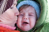 Grandmother kissing crying baby. — Stock Photo