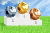 Football balls on podium among green grass. — Foto de Stock