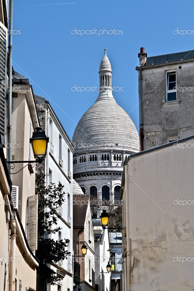 A view of the Sacre Coeur dome from an alley with brightly colored yellow lampposts in Montmartre, the hilltop region of Paris. — Photo #9269458