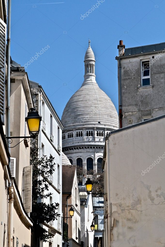 A view of the Sacre Coeur dome from an alley with brightly colored yellow lampposts in Montmartre, the hilltop region of Paris. — Stockfoto #9269458