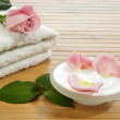 Spa essentials (cream, white towel and pink rose) - Stock Photo