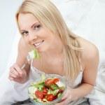 Beautiful woman eating green salad — Stock Photo