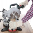 Worker cutting timber using circular saw - Stock Photo