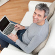 Senior man sitting in sofa and using laptop - Stock Photo