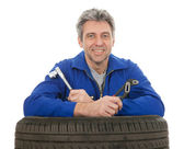 Automechanic leaning on car tires — Stock Photo