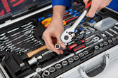 Portrait of automechanic taking a wrench out of toolbox — Stock Photo