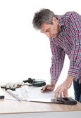 Worker looking into a house plan — Stock Photo