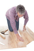 Worker assembling laminate floor — Stock Photo