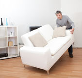 Senior man moving sofa — Stock Photo