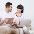Young couple using laptops in couch — Stock Photo