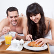 Young couple eating breakfast in bed — Stock Photo #9858815