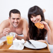 Young couple eating breakfast in bed — Stock Photo