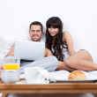Young couple lying up in bed with laptop — Stock Photo