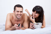 Young couple lying up in bed and watching TV — Stock Photo