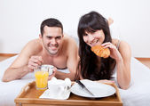 Young couple eating breakfast in bed — Stok fotoğraf
