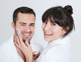 Playful young couple applying cream — Stock Photo