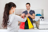 Customer buying clothes in shop — Stock Photo