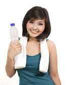 Healthy girl holding a bottle of drink after exercise — Stock Photo