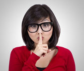 Pretty teenage girl wearing nerd glasses making silence sign — Stock Photo