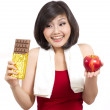 Young woman after exercise holding chocolate and apple making a choice — Stock Photo