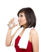 Pretty young female drinking water after exercise — Stock Photo